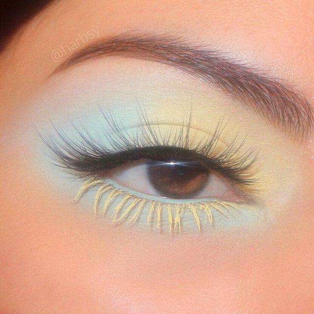 Foto de um olho. Ele está com uma sombra azul e amarelo pastel, com cílios postiços e rímel amarelo nos cílios inferiores.