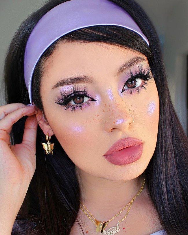 Selfie de uma mulher. Ela usa colares dourados, brinco dourado, faixa de cabelo lilás e maquiagem com sombra e iluminador lilás. Ela está com a mão direita perto da orelha, olha para a câmera e não sorri.
