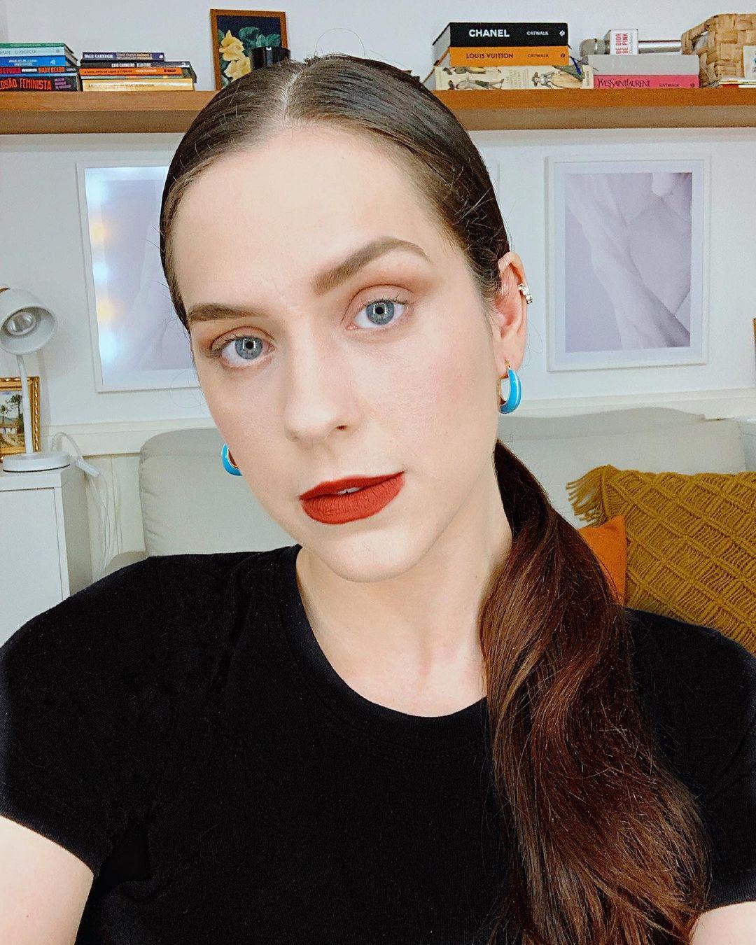 Selfie de Sophia Abrahão; ela está sorrindo levemente com camiseta preta, cabelo preso, brincos azuis e batom vermelho