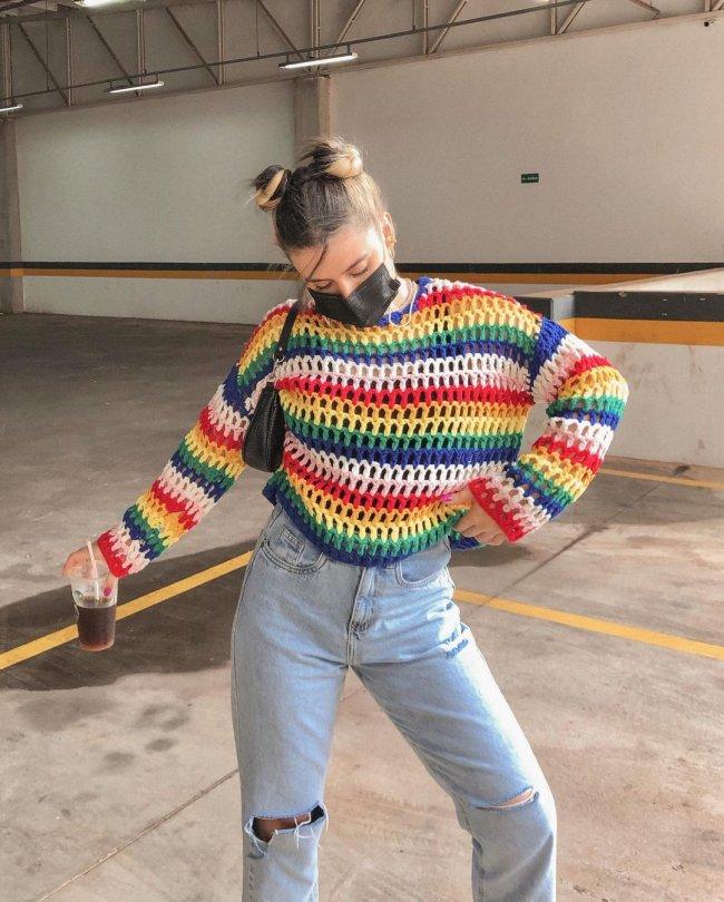 Foto da influencer Lorrine Mondin em um estacionamento. Ela usa uma blusa de tricô colorida, calça jeans, máscara preta e penteado space buns. Ela está segurando um copo com a mão direita, com a mão esquerda na cintura e olha para baixo.