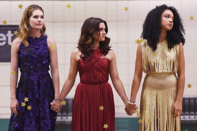 Cena de The Bold Type com as três protagonistas - Sutton, Jane e Kat - usando vestidos de festa (roxo, vermelho e dourado, respectivamente) em uma estação de metrô em Nova Iorque; elas estão na plataforma de mãos dadas olhando para a direção dos trilhos enquanto esperam o trem