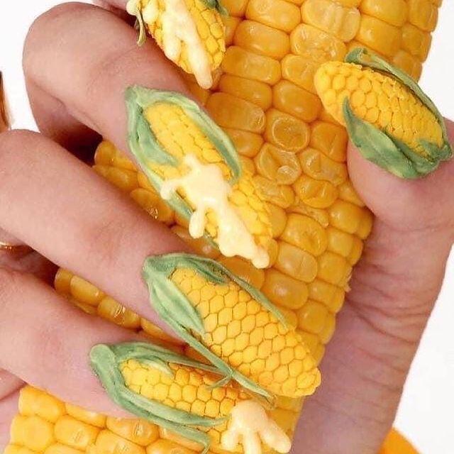 Foto com destaque nas unhas que estão com nail art inspirada em milho