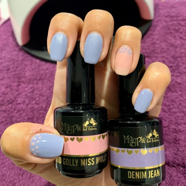 Foto com destaque nas unhas com nail art de bolinha, dessa vez com fundo lilás e bolinhas brancas.