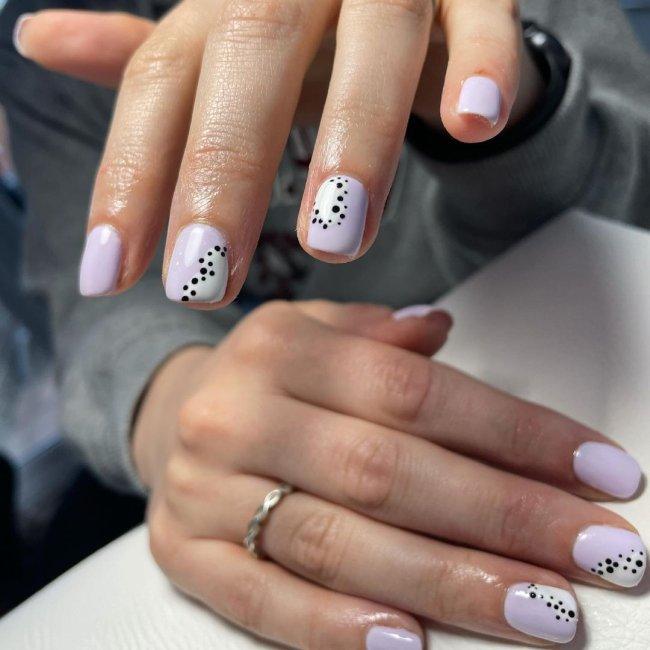 Foto com destaque nas unhas com nail art de bolinha, dessa vez com fundo lilás e bolinhas pretas.