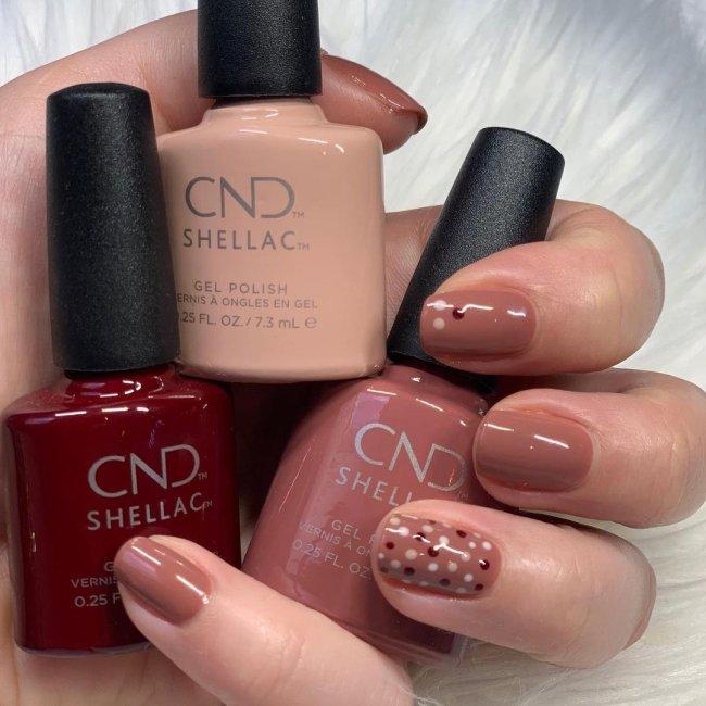 Foto com destaque nas unhas com nail art de bolinha, dessa vez com fundo marrom e bolinhas vermelhas e bege.