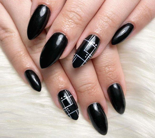 Foto com destaque nas unhas com nail art de bolinha, dessa vez com fundo preto, listra branca e bolinhas.