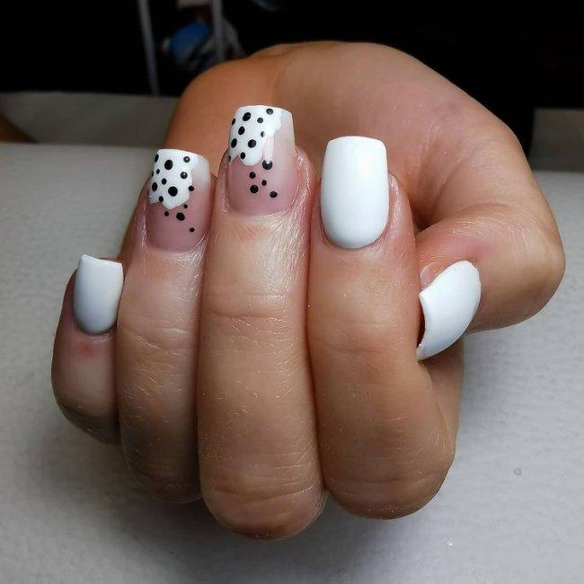 Foto com destaque nas unhas com nail art de bolinha, dessa vez com fundo branco e bolinhas pretas.