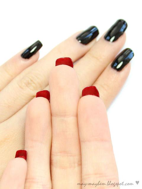 Foto com destaque para mãos, unha preta com interior vermelho