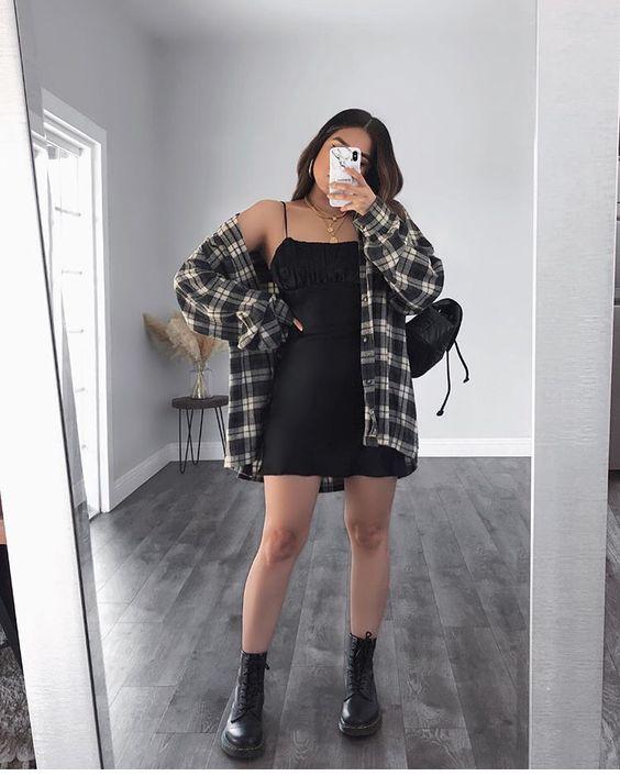Selfie no espelho de uma mulher. Ela usa um vestido preto curto, camisa xadrez oversized, coturno preto e bolsa preta.