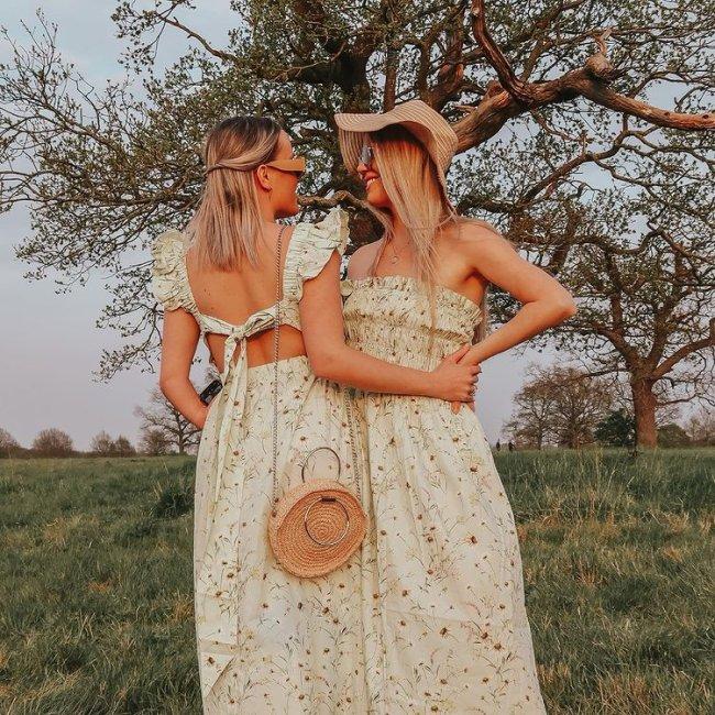 Casal posa em frente a arvores em chão com gramado, as duas estão se olhando e o cabelo cobre suas expressões faciais. Uma está de lado para a câmera e a outra de costas. As duas usam vestido com estampa floral igual.
