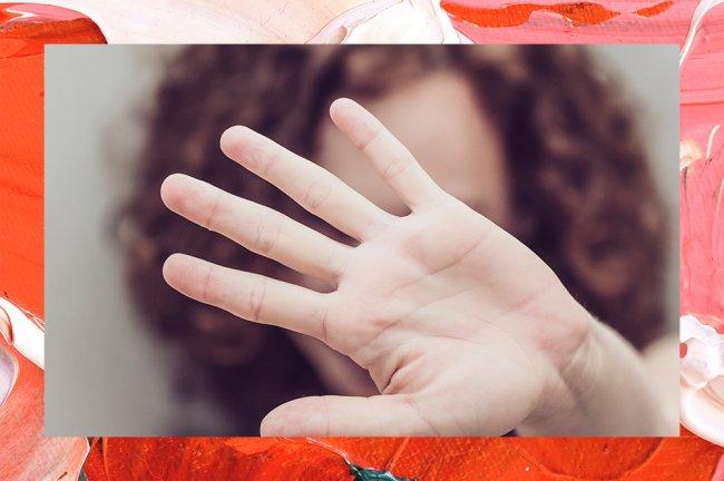 Mulher ruiva com a mão levantada em frente ao rosto, fazendo sinal de