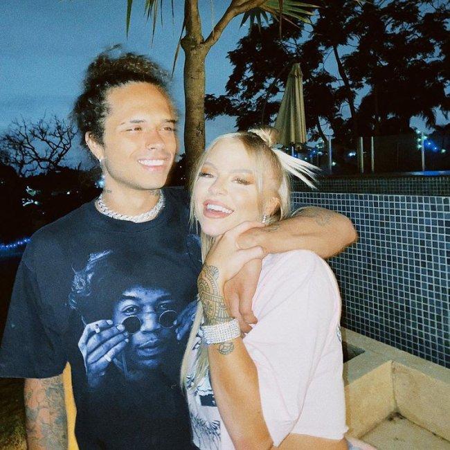 Foto de Vitão e Luísa Sonza; ele está com o braço em volta do pescoço da cantora; os dois estão sorrindo e a foto está um pouco borrada, como se eles estivessem se mexendo quando foi tirada