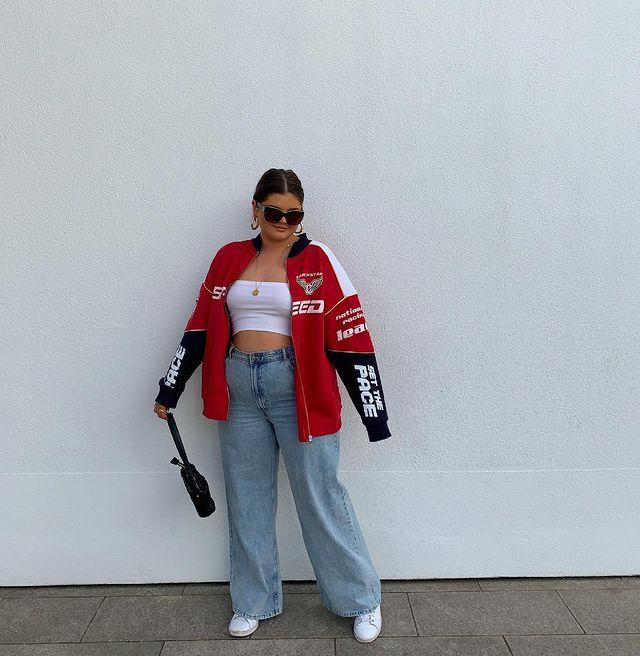 Garota usando top cropped branco, calça jeans wide leg, tênis branco e jaqueta oversized vermelha, preta e branca. Ela está segurando uma bolsa preta com uma das mãos, olhando para baixo e usando um óculos de sol.
