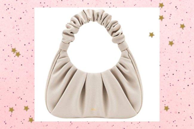 Foto com destaque na bolsa bege da marca JW PEI, ela é pequena e tem a alça levemente enrugada.
