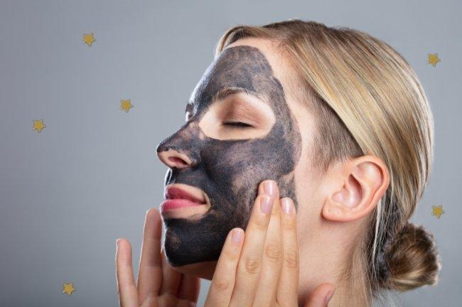 Mulher passando carvão ativado no rosto com os olhos fechados.