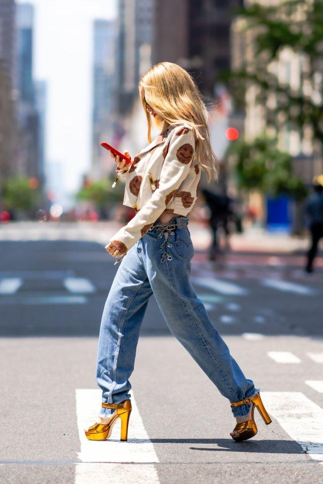 Foto da atriz e cantora Dove Cameron de lado, caminhando em uma rua. Ela está olhando para seu celular, usando jaqueta e calça jeans.