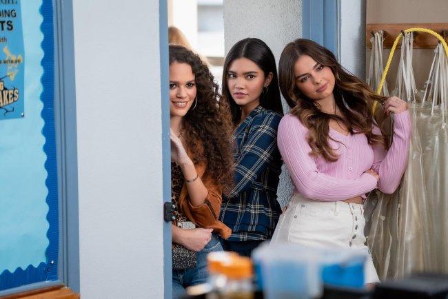 Madison Pettis, Manneepat Molloy, Addison Rae em cena de Ele É Demais (He's All That); as três estão encostadas na porta da sala de aula na escola observando algo enquanto sorriem com expressões de vilãs