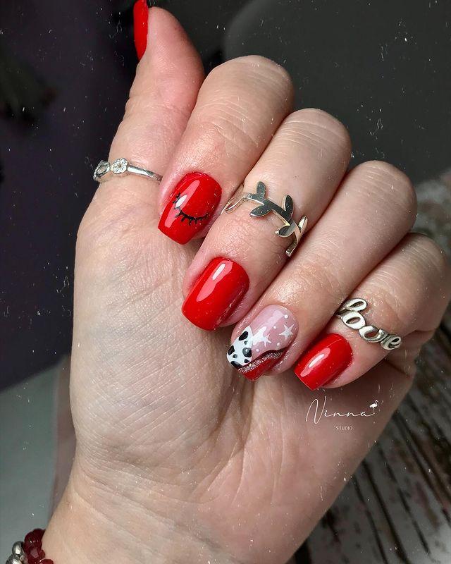 Foto com close em mão com os dedos fechados dando destaque para o design das unhas com esmalte vermelho, preto e branco.