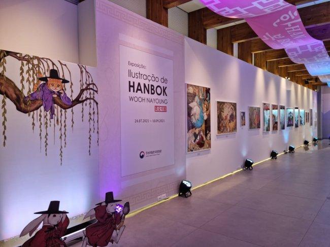 Imagem da Exposição Woo NaYoung; uma parede branca com luzes em tons de rosa/roxo iluminam as artes expostas