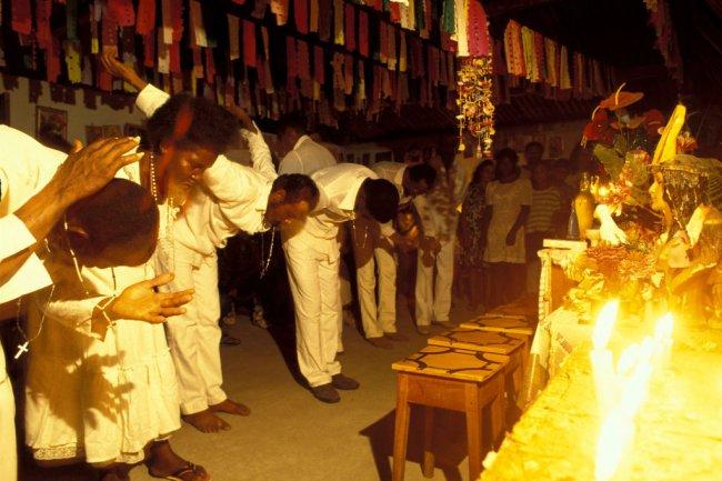 Imagem mostra um culto de candomblé realizado na Bahia. Negros vestidos de brancos se curvam em frente a estátuas de santos.