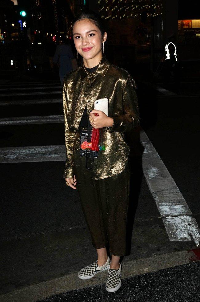 Olivia Rodrigo posando com expressão sorridente usando blusa dourada com calça preta.