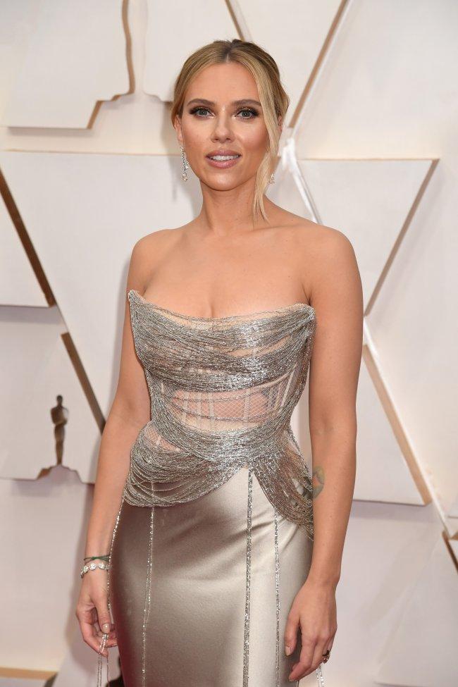 Scarlett Johansson posando no carpet do Oscar 2020; ela está usando um vestido prata sem alças e sorrindo para a câmera com os braços soltos ao lado do corpo