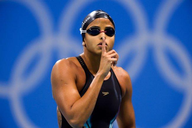 Foto de Etiene Medeiros nas Olimpíadas do Rio de Janeiro. Ele veste maiô e touca pretos, e faz sinal de silêncio com o dedo indicador sobre a boca
