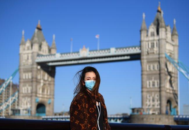 Mulher com máscara posa na frente da Tower Bridge, em Londres