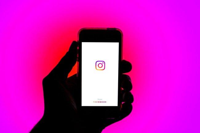 Foto de uma mão segurando um celular apresentando o logo do Instagram. Fundo é pink.