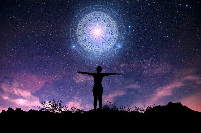 A silhueta de uma mulher de costas, com os braços abertos. Sobre ela, um círculos com os signos do zodíaco. O fundo é azul e roxo.