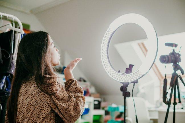 Uma moça, que é influenciadora digital, mandando beijinho pra câmera enquanto grava um conteúdo em seu quarto