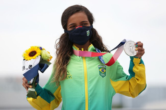 Rayssa Leal no pódio de Tóquio 2020, segundado sua medalha de prata e um buquê de girassóis