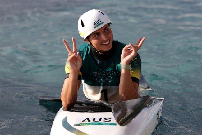 A australiana Jessica Fox comemorando seu feito em Tóquio. Ela está de capacete branco, sentada em uma caiaque, no mar, fazendo sinal de paz e amor com as mãos