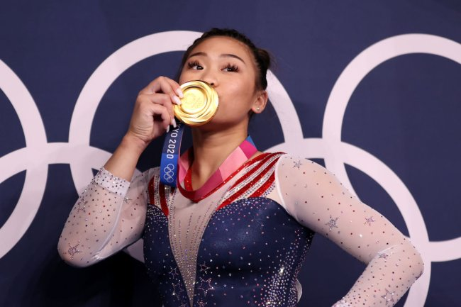 A hmong Sunisa Lee, dos EUA, beijando sua medalha de ouro após vencer os individuais gerais da ginástica; ela está com uma das mãos na cintura e veste um collant azul, branco e vermelho bastante brilhante