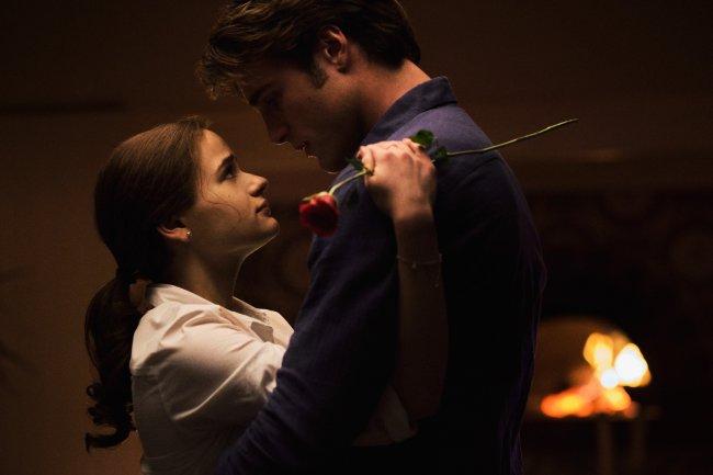 Joey King como Elle e Jacob Elordi como Noah em cena de A Barraca do Beijo 3; os dois estão abraçados se encarando em um ambiente à meia luz; Elle está com uma roupa branca segurando uma rosa e Noah está de camisa azul escura
