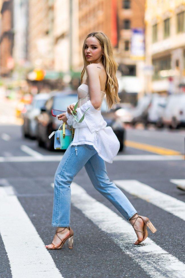 Dove Cameron com óculos verde, corset, calça jeans e camisa branca. Sua expressão é séria. Ela está de lado com o rosto virado para a câmera, atravessando a rua.