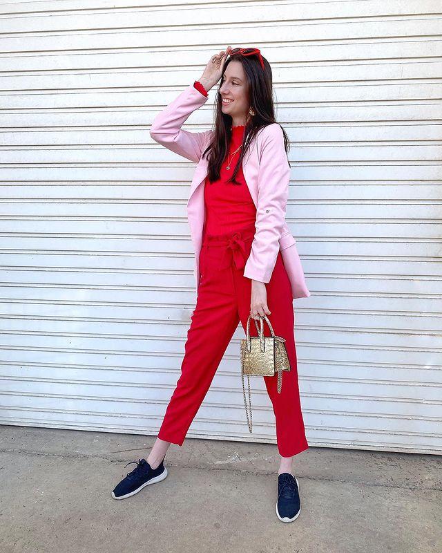 Jovem posando em frente a parede branca com blazer rosa claro, uma das mãos apoiadas na cabeça e segurando uma bolsinha com tênis preto.