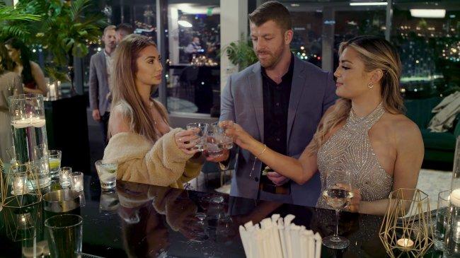 Francesca, Giannina e Damian em especial de Casamento às Cegas (Love is Blind); os três estão se olhando desconfortáveis enquanto fazem um brinde juntos