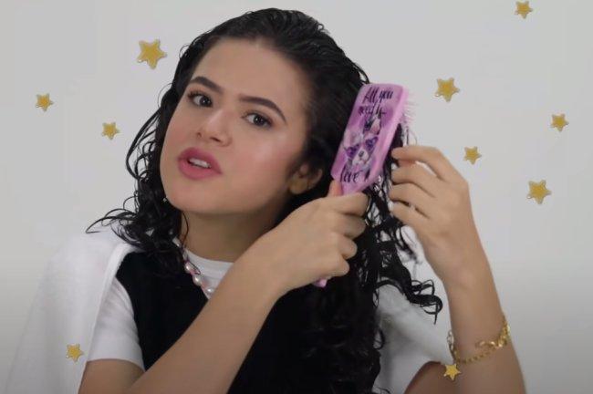 Print de vídeo do youtube no qual Maisa finaliza seu cabelo. Ela usa blusa branca com suéter preto, penteia seu cabelo com escova branca e usa colar de miçanga.