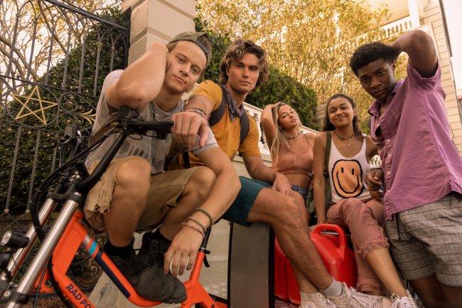 JJ, John B. Sarah, Kiara e Pope em cena da segunda temporada de Outer Banks; eles estão posando para câmera sorrindo levemente em uma bicicleta