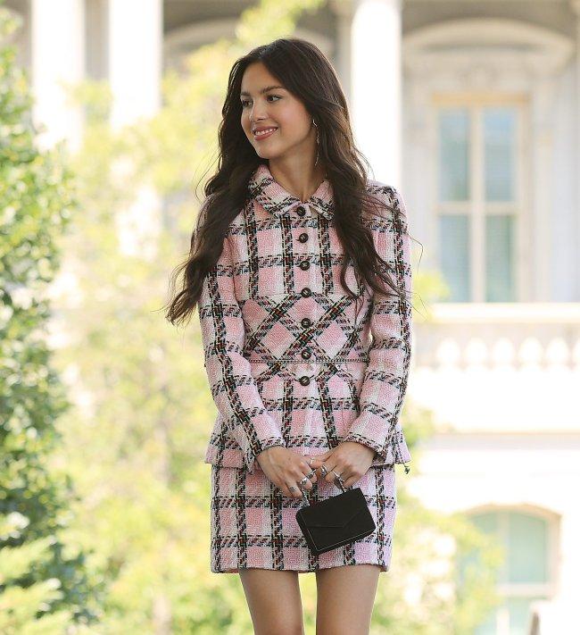 Olivia Rodrigo sorridente segurando uma pequena bolsa preta e com conjunto xadrez rosa e preto.