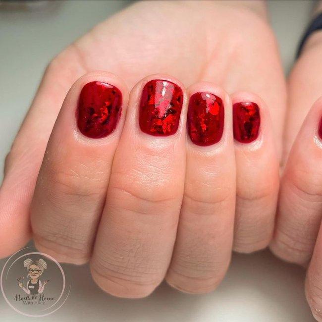 Foto com close em uma mão fechada mostrando os dedos, nas unhas esmalte vermelho com glitter.