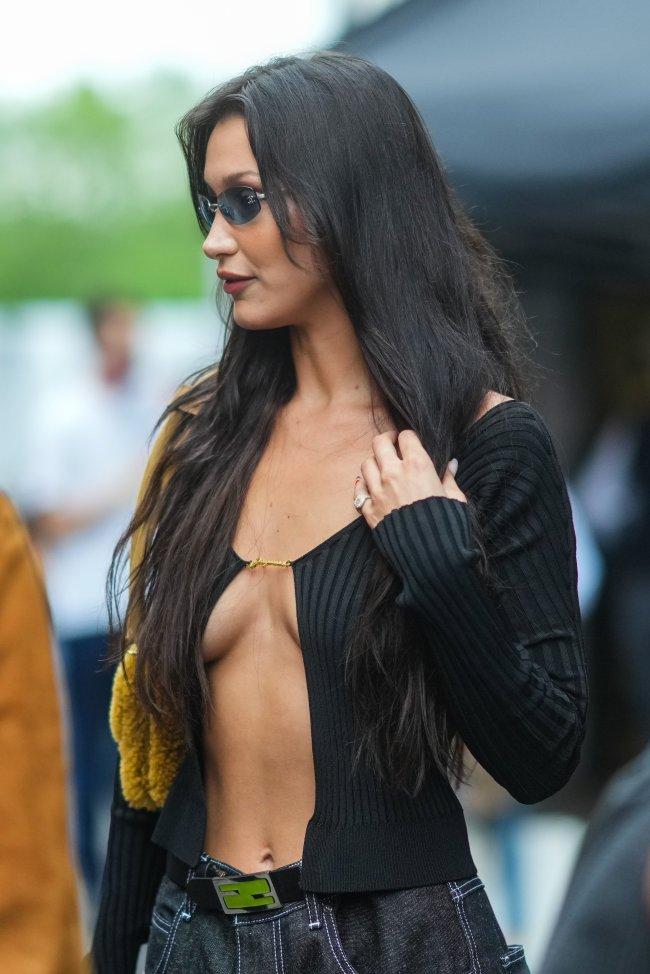 Foto da modelo Bella Hadid. Ela usa uma blusa preta com decote aberto com detalhe de alfinete, calça jeans, óculos de sol e bolsa de pelinhos amarela. Ela olha para o lado e não sorri.