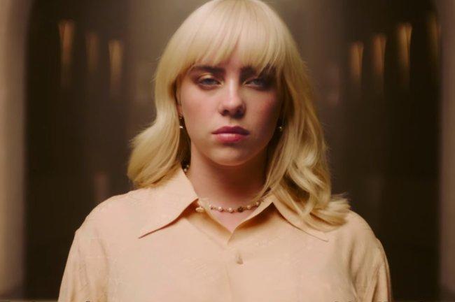 Billie Eilish usando camisa amarela, com expressão facial séria olhando para a câmera. Está de cabelo médio e franjinha em loiro platinado