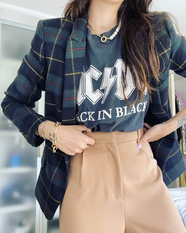 Na imagem só conseguimos ver do pescoço para baixo. Uma jovem mostra seu visual composto por uma camiseta de banda, blazer xadrez e calça de alfaiataria.