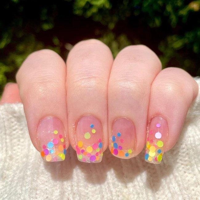 Foto com close nas unhas e tem nail art com bolinhas coloridas nas cores, azul, verde, rosa, amarelo.