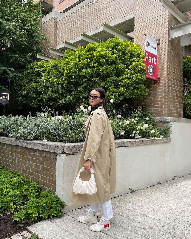 Jovem posando em frente a muro com plantas, ela está de lado usando óculos escuros pretos e com expressão séria. Ela usa blusa bege e calça jeans clara.