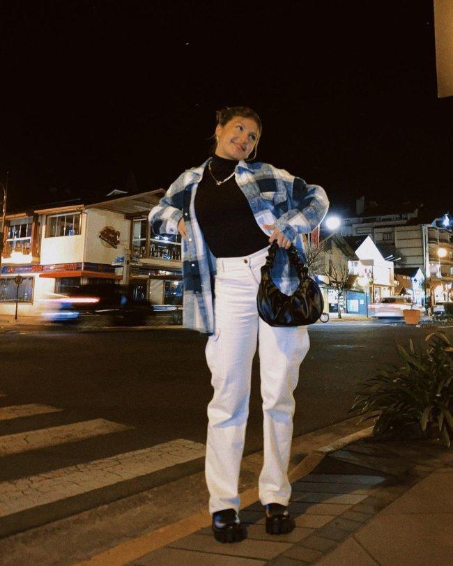 Jovem posando na rua com as mãos na cintura, usando camisa xadrez com calça branca e bolsa preta. Sua expressão é sorridente.