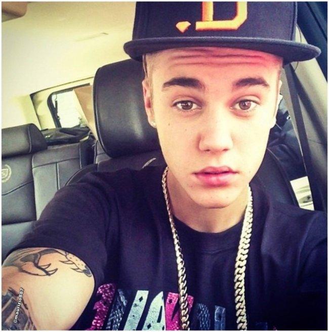 Selfie do cantor Justin Bieber. Ele usa uma camiseta preta, corrente dourada e boné de aba reta. Olha para a câmera mas não sorri.