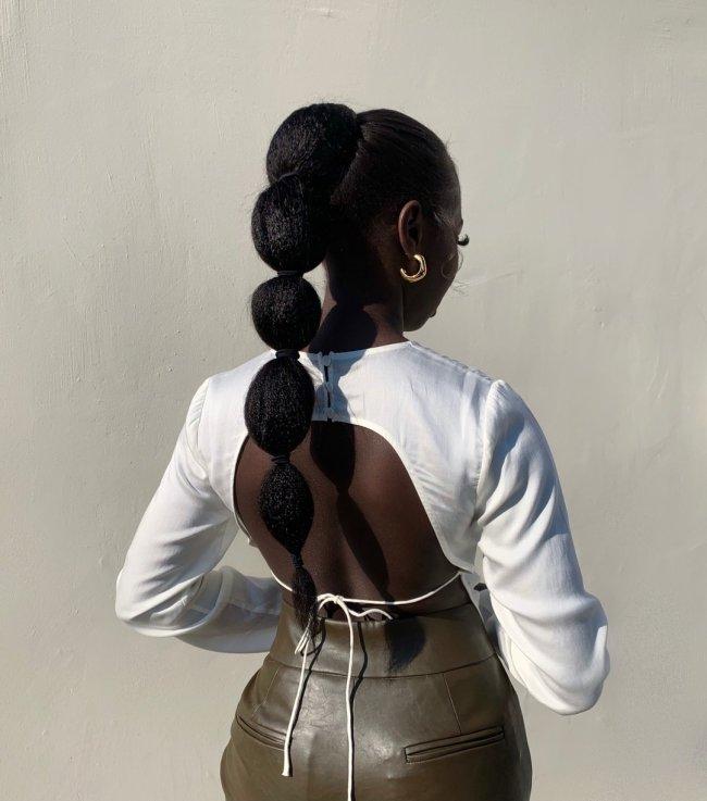 Jovem posando de costas usando blusa branca e calça marrom.